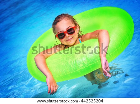 Cute little girl swimming in the pool in big bright green rubber ring, having fun in aquapark, happy summer holidays on the beach - stock photo