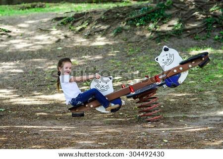 Cute little girl swinging on seesaw in public park - stock photo