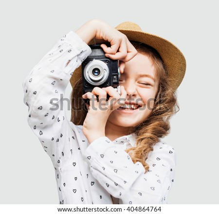 Cute little girl takes picture with vintage camera - stock photo