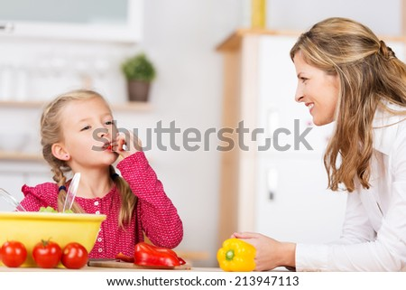 Cute little girl tasting the vegetables as she prepares a meal with her mother in the kitchen chewing on a ripe red cherry tomato with a look of bliss