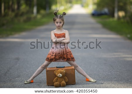 Cute little girl traveller with Teddy bear and  suitcase on the road. - stock photo