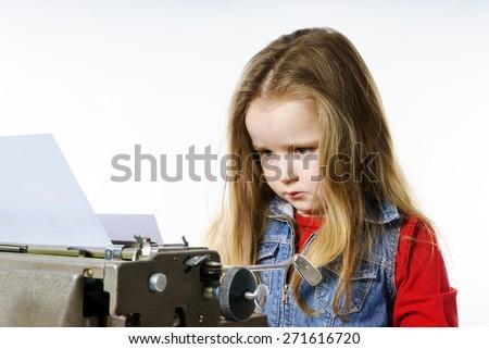 Cute little girl typing letter on vintage typewriter keyboard - stock photo