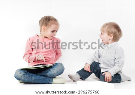 Cute little girl uses a tablet and boy laughing and playing with chalk and paper - stock photo