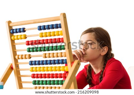 Cute little girl using an abacus on white background - stock photo