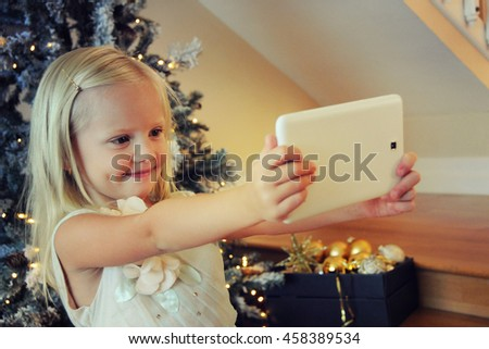 cute little girl using digital tablet while sitting  at christmas tree - stock photo