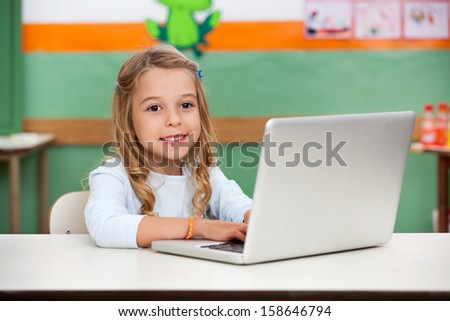 Cute little girl using laptop at desk in classroom - stock photo