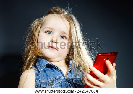 Cute little girl using modern red smartphone. Telecommunication industry concept. - stock photo
