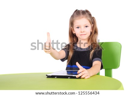 cute little girl using tablet PC with the thumbs up - stock photo