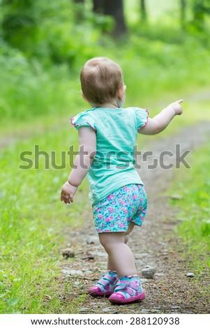 Cute Little girl walking away on the road ahead, looking back - stock photo