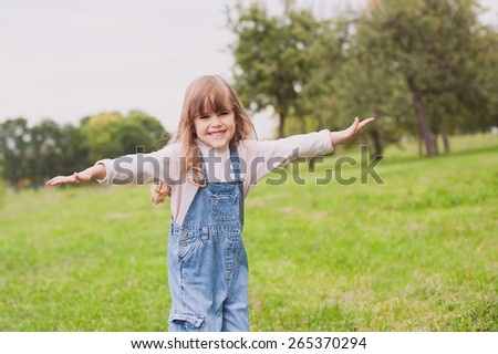 Cute little girl walking in the park - stock photo