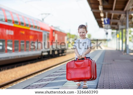 Cute little girl walking with big red suitcase on a railway station. Kid waiting for train and happy about a journey. People, travel, lifestyle concept - stock photo