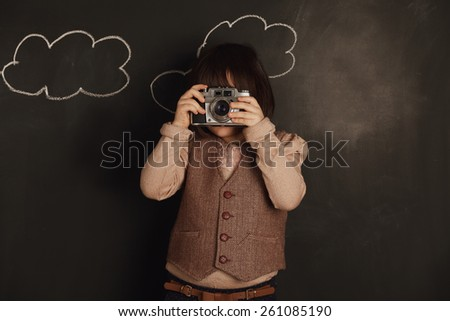 cute little girl wants to be a photographer - stock photo