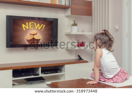 cute little girl watching advertisement on tv - stock photo