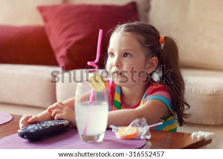 cute little girl watching tv and having lemonade and candy at home.