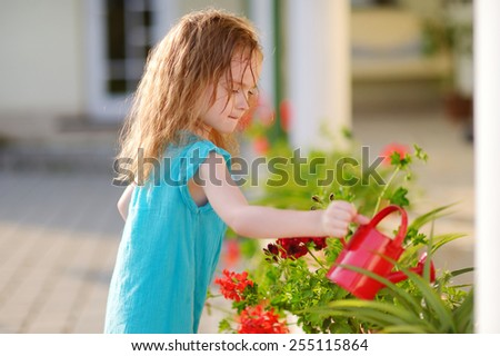 Cute little girl watering flowers in the garden on beautiful summer day - stock photo