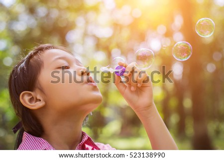 Cute little girl wearing a pink shirt blowing bubbles in the park,vintage style.