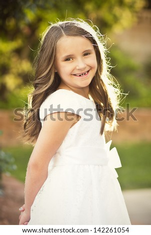 Cute little girl wearing a white dress - stock photo