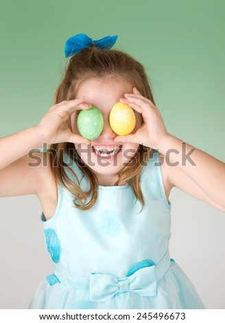 Cute Little Girl wearing an Easter dress with dyed eggs in front of her eyes and a big smile