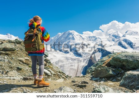 Cute little girl wearing backpack and colorful coat, standing in front of Gornergrat glacier, Switzerland, back view - stock photo