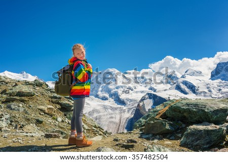 Cute little girl wearing bright rainbow colored coat, backpack and beige boots, standing in front of Gornergrat glacier, Switzerland - stock photo