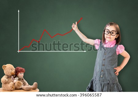 Cute little girl wearing business dress and showing graph on green chalk board.