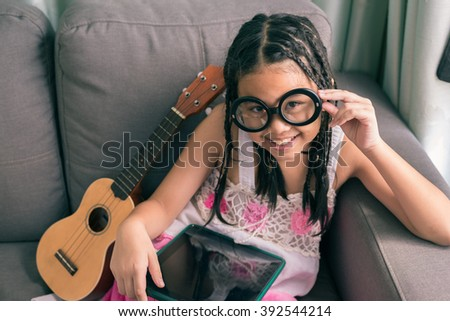 Cute little girl,wearing glasses,dreadlocks hair style ,playing with computer at home laying on sofa  - stock photo