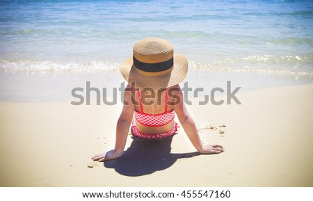 Cute little girl wearing hat sitting at the tropical beach