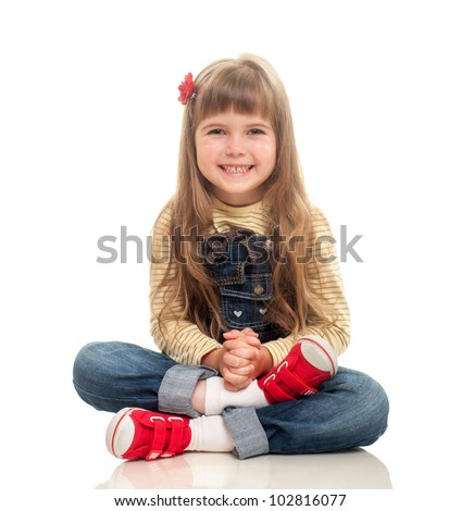 cute little girl wearing jeans overall sitting on the floor and smiling on white background