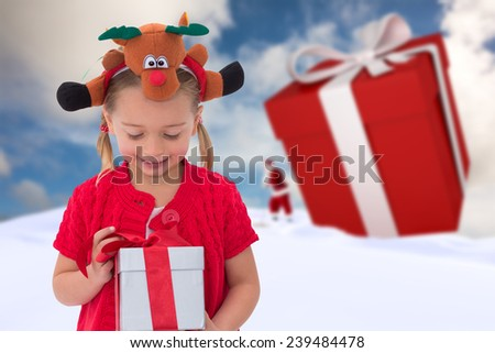 Cute little girl wearing rudolph headband against blue sky with white clouds - stock photo