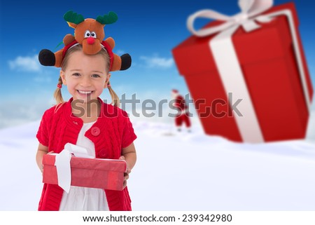 Cute little girl wearing rudolph headband against bright blue sky over clouds - stock photo