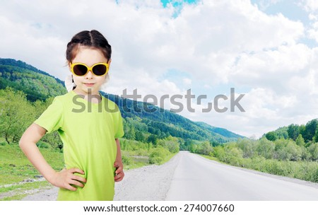 Cute little girl wearing sunglasses stands on the roadside - stock photo