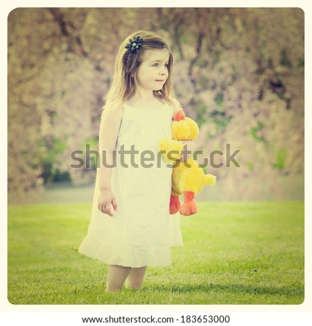 Cute little girl wearing white dress outside with Instagram effect filter - stock photo