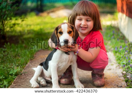 Cute little girl with a beagle puppy. - stock photo
