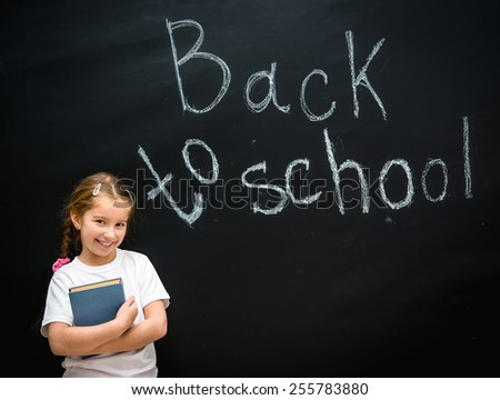 cute little girl with a blue book in hand smiling on black background blackboard on which the back to school - stock photo