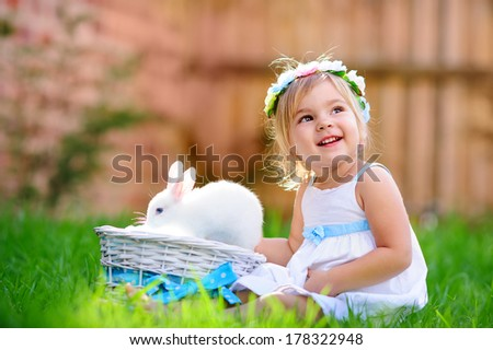 Cute little girl with a bunny rabbit has a easter at green grass background - stock photo