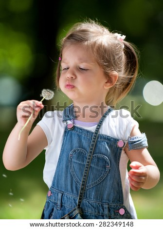 Cute little girl with a Dandelion. Cute little girl blowing dandelion in the green spring grass - stock photo