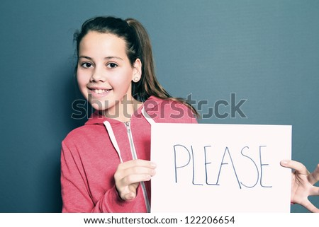 Cute little girl with a happy grin holding up a sheet of white paper with a handwritten note saying PLEASE, studio portrait on grey - stock photo