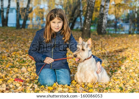 Cute little girl with a Scottish Terrier dog sitting on the autumn leaves