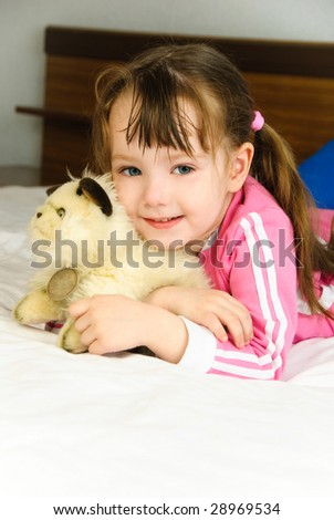 cute little girl with a toy on the bed at home - stock photo