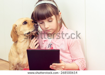 Cute little girl with a yellow dog playing on a tablet - stock photo