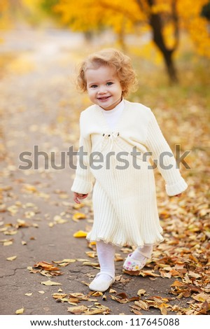 Cute little girl with autumn leaves in the park - stock photo