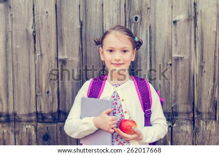 Cute little girl with backpack, holding a book and red apple, standing against wooden background, back to school concept, toned image, vintage effect - stock photo