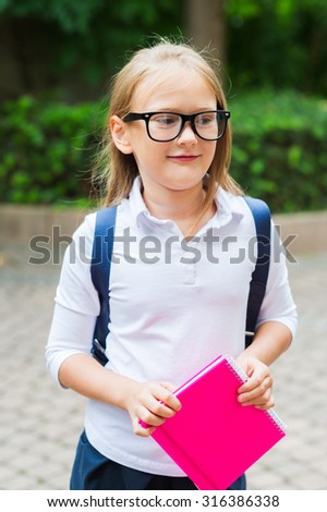 Cute little girl with backpack, holding a pink notebook, outdoor portrait, wearing white top and black  - stock photo