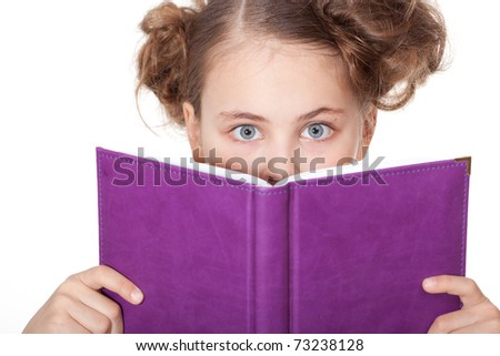 Cute little girl with beautiful eyes peeping behind the book