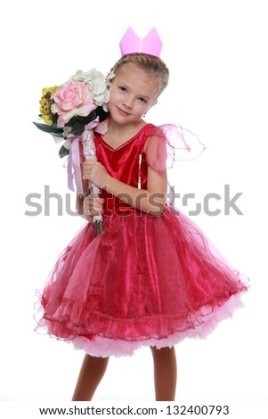 Cute little girl with beautiful hair and a crown in a red dress holding a big beautiful bouquet on Holiday