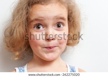 Cute little girl with big eyes looking surprised. She looks ahead on a background white wall. - stock photo