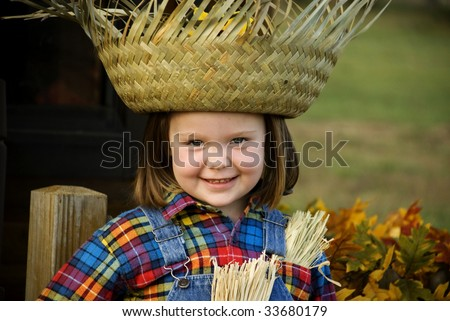 Cute little girl  with big smile, in a Halloween scarecrow costume, wearing a big straw hat, with fall decorations, horizontal with copy space, shallow depth of field - stock photo