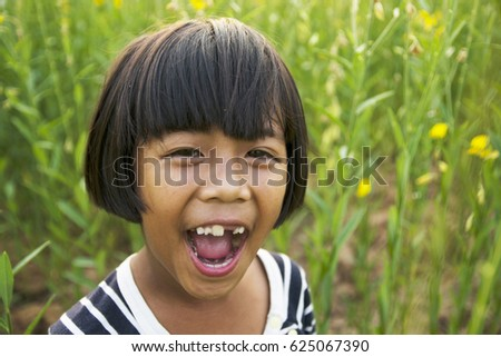 cute little girl with big smile in  field