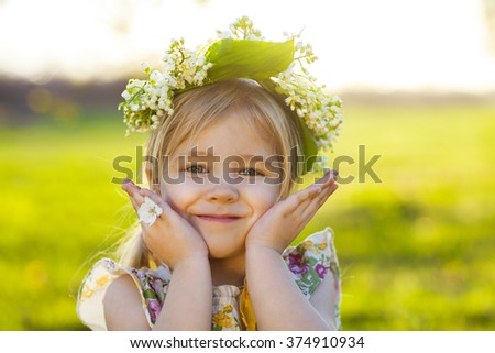 Cute little girl with blond hair in a wreath of lily of the valley in the spring garden