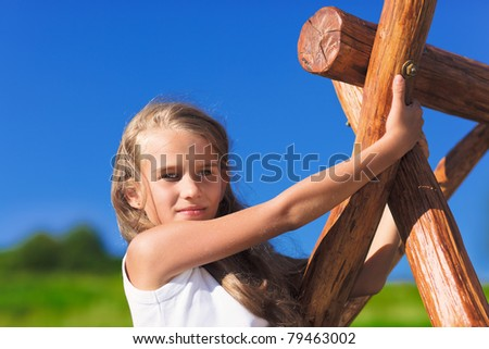 Cute little girl with blond long hair playing on wooden chain swing
